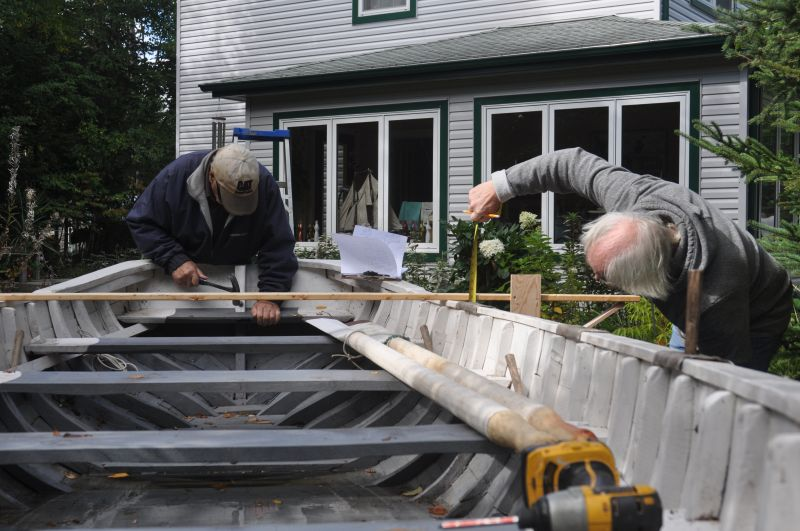Jerome Canning and Jack Casey taking measurement's of a row boat built by Jack in 2012.