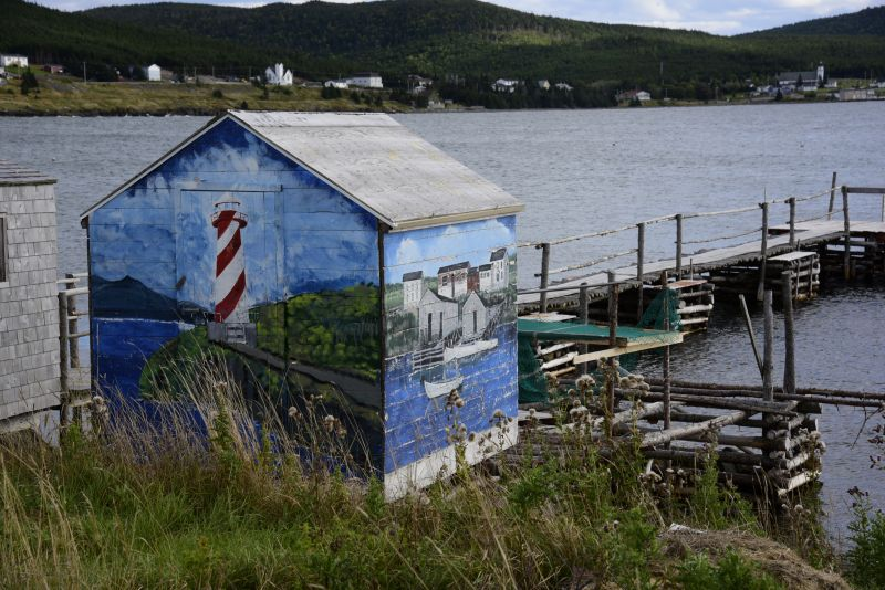 Aside from boatbuilding, Edwin loves to paint. His small stage sits on the shoreline in Heart's Delight full of colorful imagery related to fishing and Trinity Bay.