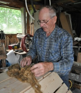 Tom Abbott displays oakum that can be rolled into strands and used to cork the seams of the boat