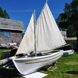 Wooden punt built by Earl Feltham recently fiberglassed. Originally built with juniper laths and spruce keel, stem, stern, and knees. Before being fiberglassed, Earl removed the wooden knees and extended the keel. Sail was made by Earl c. 2000